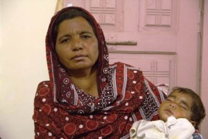 Parveen Bibi, sister of the murdered husband, holds the dead couple's baby - one of four children orphaned by the killing 4 Nov Punjab, Pakistan (Photo: Asif Aqeel)